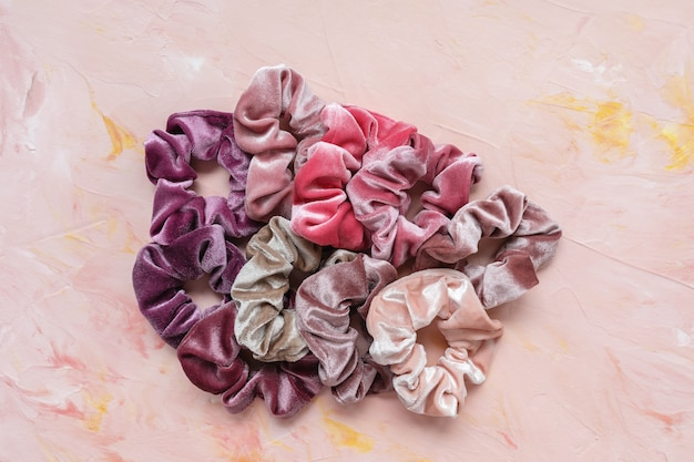 Collectie trendy fluwelen scrunchies op roze achtergrond. diy accessoires en kapsels concept, kopie ruimte Premium Foto