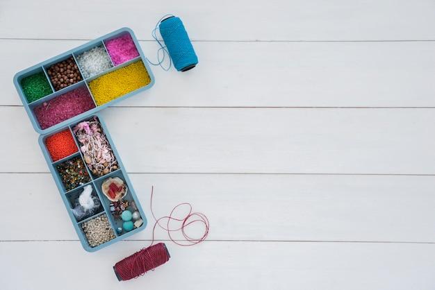 Collectie van kralen in blauwe behuizing met helder blauwe en paarse garen spoel op witte bureau Gratis Foto