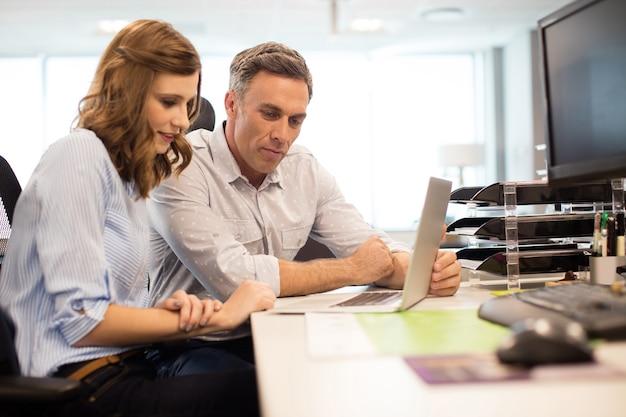 Collega's die aan laptop bij bureau werken Premium Foto