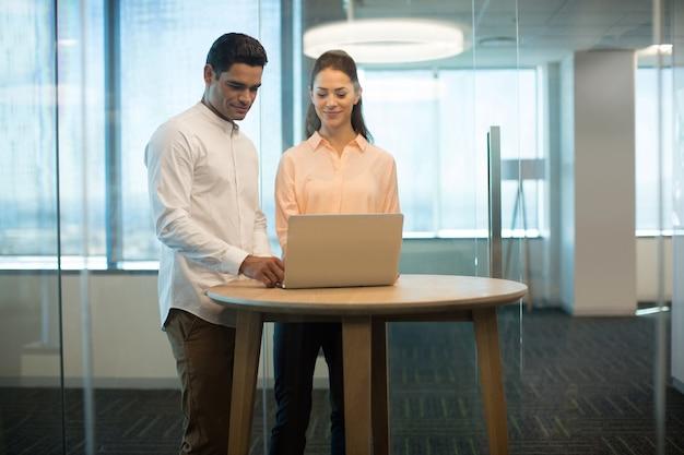 Collega's met behulp van laptop in moderne kantoren Premium Foto