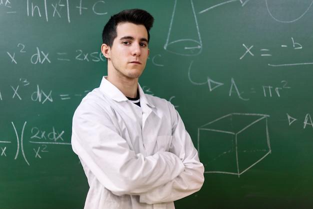 College student in laboratorium klas. college student met witte jas, staande voor schoolbord. Premium Foto