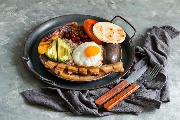Colombiaans eten. bandeja paisa, typisch gerecht in de antioquia-regio van colombia - chicharron (gebakken varkensbuik), bloedworst, worst, arepa, bonen, gebakken weegbree Premium Foto