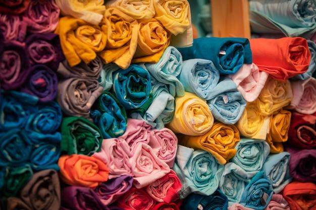 Colorsful abstract roll t-shirt close-up detail van veelkleurige stof textuur op plank. Premium Foto