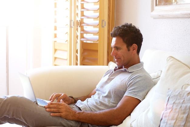 Comfortabele man om thuis te zitten met laptop Premium Foto