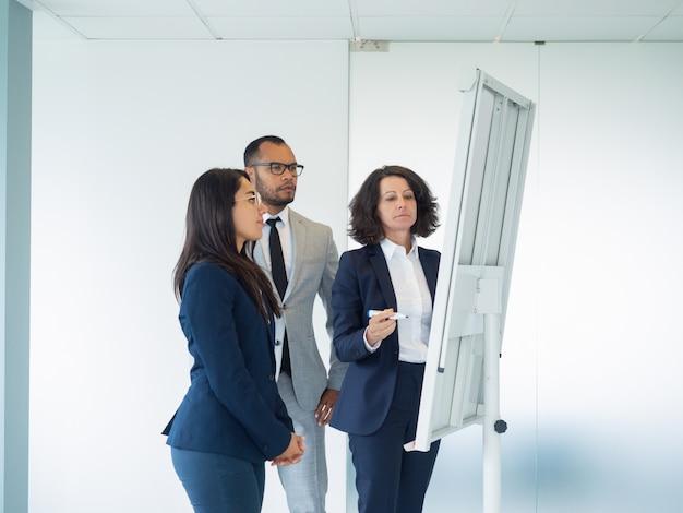 Commerciële groep van drie die trekkend op whiteboard bestuderen Gratis Foto