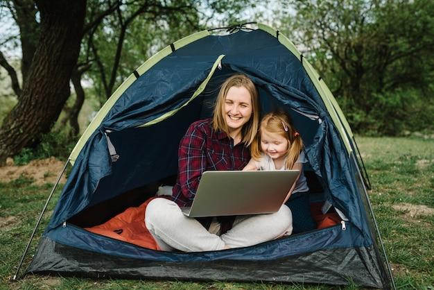 Communiceer met familie, familie online op laptop in tent in de natuur. vrouw werknemer spreken praten over videogesprek met collega's. moeder die met kind werkt. kind maakt lawaai en stoort moeder. Premium Foto