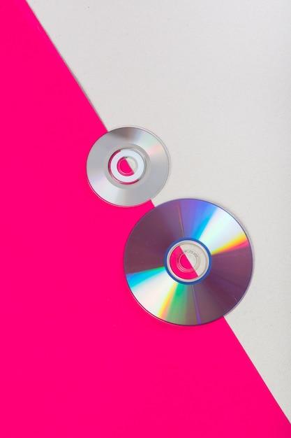Compact-discs op een roze en witte dubbele achtergrond Gratis Foto