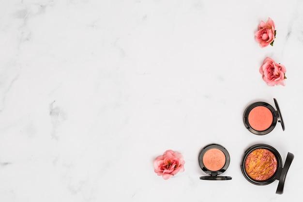 Compact gezichtspoeder met roze roos op marmeren gestructureerde achtergrond Gratis Foto