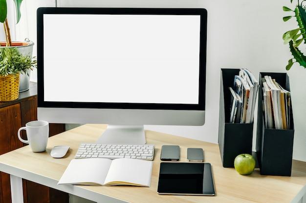 Computermonitor met mockup wit scherm op kantoor tafel met benodigdheden Premium Foto
