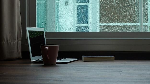 Computernotitieboekje naast een kopkoffie op de regenachtige achtergrond van het dagvenster Premium Foto