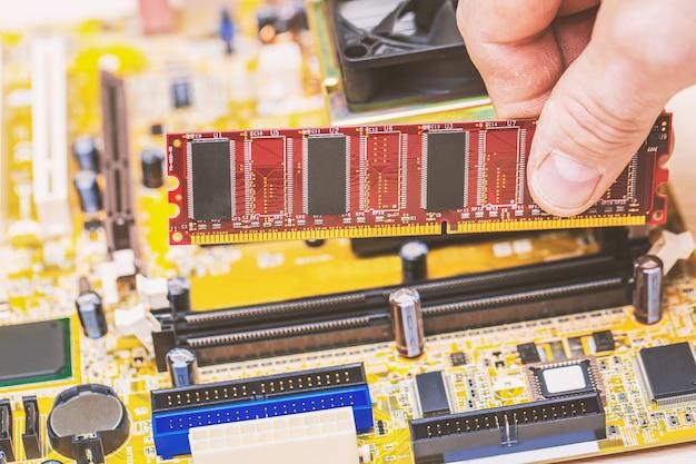 Computertechnicus die computergeheugen ram installeert in de sleuf van het moederbord Premium Foto