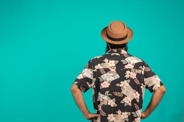 Concept achter de mannelijke toeristen die een hoed op een blauw dragen. Gratis Foto