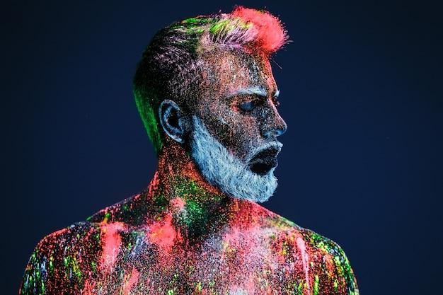Concept. een bebaarde man in kapperszaak. een stijlvolle bebaarde man is getrimd in barber shop. de man is versierd met ultraviolet poeder. Premium Foto