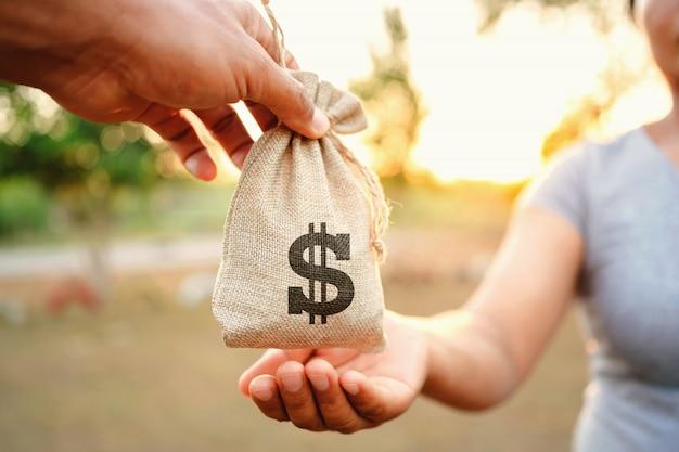 Concept financiële boekhouding. hand geven geld tas voor vrouw Premium Foto