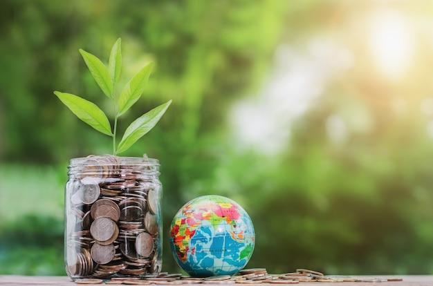 Concept geld met plant groeit op munt in pot en globe speelgoed Premium Foto