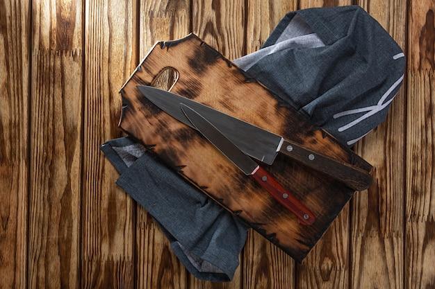 Concept koken, koken. twee keukenmessen op een snijplank en een servet op een houten tafel, bovenaanzicht. Premium Foto
