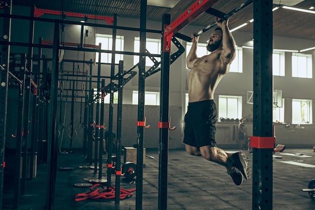 Concept: kracht, kracht, gezonde levensstijl, sport. krachtige aantrekkelijke gespierde man op sportschool Gratis Foto
