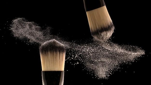 Concept, make-up. twee borstelmakers strooien poeder uit Premium Foto
