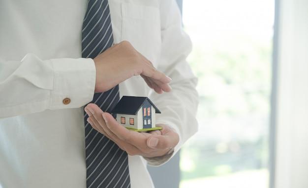 Concept onroerendgoedverzekering: verzekeringsagent houdt een huismodel in de hand met het symbool van een opstalverzekering. Premium Foto