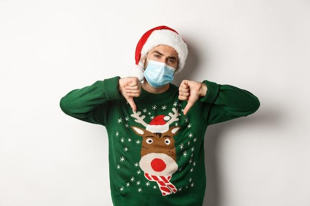 Concept van covid-19 en kerstvakantie met knappe jonge man met een masker Premium Foto