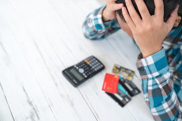 Concept van de man wordt benadrukt met schulden verschuldigd door het gebruik van een creditcard Premium Foto