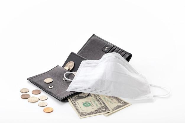 Concept van een wereldwijde crisis en dalende inkomens als gevolg van pandemisch coronavirus covid-19. portemonnee met een dollar, cent en een beschermend masker geïsoleerd. Premium Foto