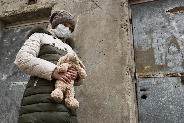 Concept van epidemie en quarantaine - een meisje met een gezichtsmasker en Premium Foto