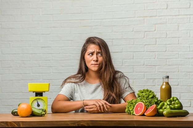 Concept van het dieet. portret van een gezonde jonge latijns-vrouw twijfelen en verward, denken aan een idee of bezorgd over iets Premium Foto