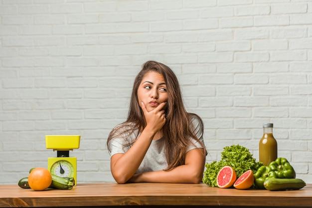 Concept van het dieet. portret van een gezonde jonge latijns-vrouw twijfelen en verward Premium Foto