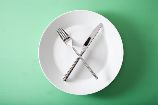 Concept van intermitterend vasten en ketogeen dieet, gewichtsverlies. vork en mes gekruist op een bord Premium Foto