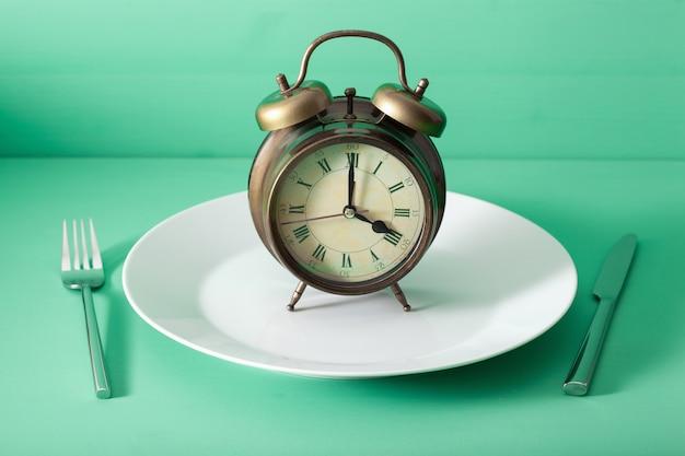 Concept van intermitterend vasten, ketogeen dieet, gewichtsverlies. vork en mes gekruist en wekker op plaat Premium Foto