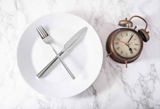 Concept van intermitterend vasten, ketogeen dieet, gewichtsverlies. vork en mes gekruist op een bord en wekker Premium Foto