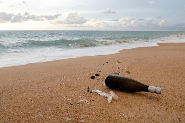 Concept van milieukwesties, bruine drankflessen en puin op het zandstrand. Premium Foto