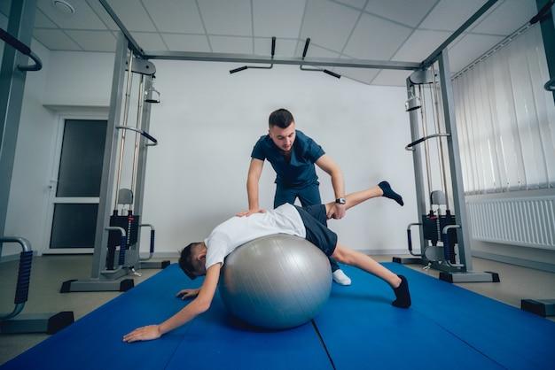 Concept van revalidatie. jonge jongen die oefeningen met bal doet onder toezicht van fysiotherapeut Premium Foto