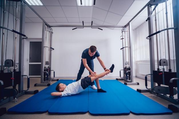Concept van revalidatie. jonge jongen die oefeningen op mat doet onder toezicht van fysiotherapeut Premium Foto