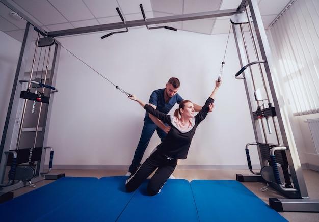 Concept van revalidatie. mooie jonge vrouw die oefeningen op mat doet onder toezicht van fysiotherapeut Premium Foto