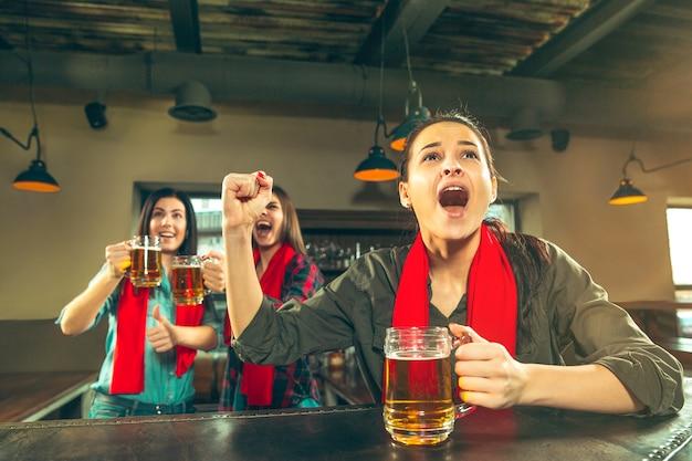 Concept van sport, mensen, vrije tijd, vriendschap, entertainment - gelukkige vrouwelijke voetbalfans of goede jonge vrienden die bier drinken, de overwinning vieren in de bar of pub. menselijke positieve emoties concept Gratis Foto