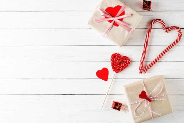 Concept van valentijnsdag. hartvormige snoep en geschenkdozen op witte houten Premium Foto