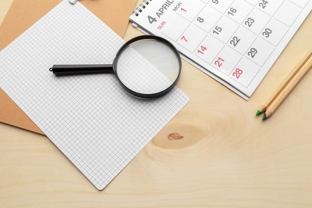Conceptenbeeld van zaken en vergaderingen. kalender om u te herinneren aan een belangrijke afspraak en vergrootglas Premium Foto