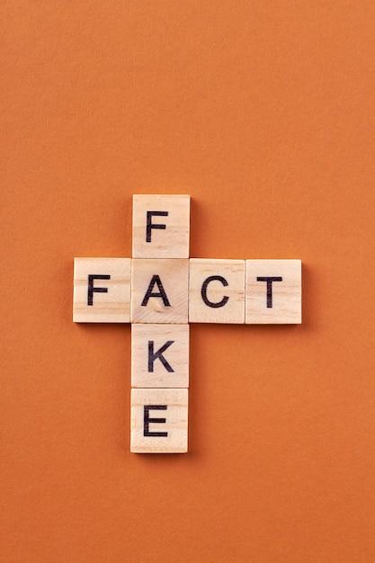 Conceptie van nieuws en informatie. kruiswoordraadsel met valse woorden en feit geïsoleerd op een oranje achtergrond. Premium Foto