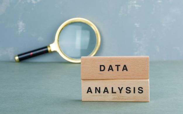 Conceptueel gegevensanalyse met houten blokken, zijaanzicht van het vergrootglas. Gratis Foto
