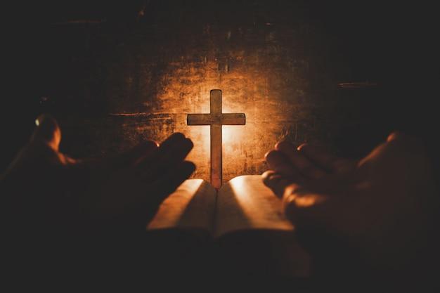 Conceptuele beeldfocus op kaarslicht met mensenhand die houten kruis op bijbel en vage wereld houden Gratis Foto