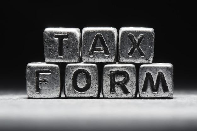 Conceptuele inscriptie belastingformulier op metalen blokjes op een zwart grijze achtergrond close-up geïsoleerd Premium Foto