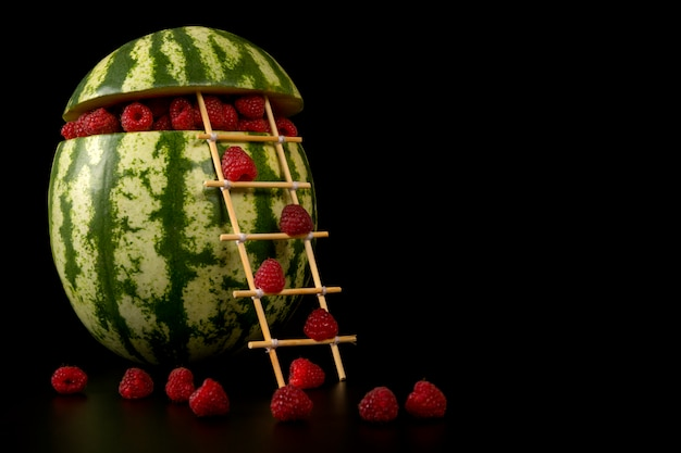 Conceptuele watermeloen gevuld met frambozen die de trap op een zwarte achtergrond beklimmen Premium Foto
