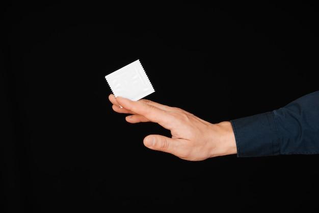 Condoom in het pakket in de hand van de man Premium Foto