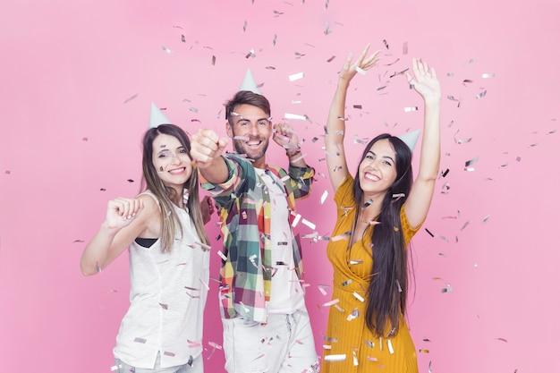 Confettien die over vrienden vallen die tegen roze achtergrond genieten van Gratis Foto