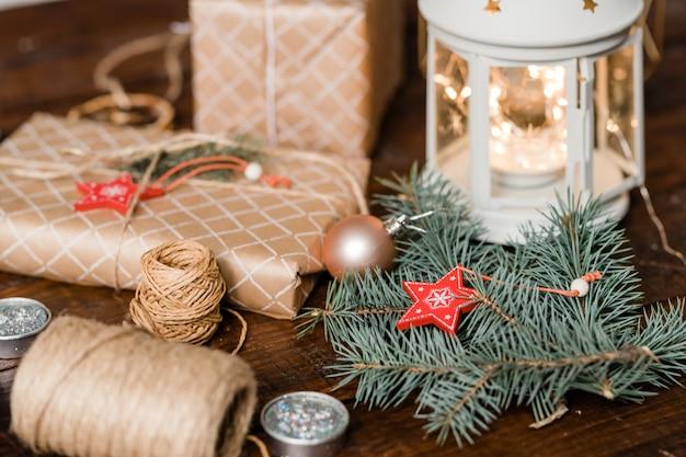 Conifeer met chrismas-sterdecoratie, ingepakte geschenkdozen, draden, kaarsen en lantaarn die vakantiesamenstelling maken Premium Foto