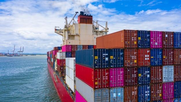 Containerschip met container voor import en export van bedrijfsvracht, luchtfoto containerschip aankomst in commerciële haven. Premium Foto
