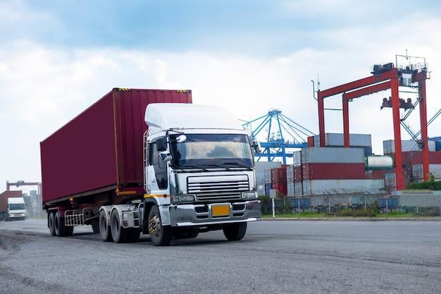 Containervrachtwagen in scheepshaven logistiek. transportindustrie in havenbedrijf. import, export logistiek industrieel Premium Foto