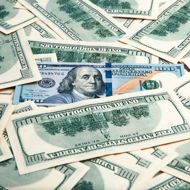 Contant geld van honderd dollarsrekeningen, dollar achtergrondafbeelding. een stapel van honderd amerikaanse bankbiljetten. Premium Foto